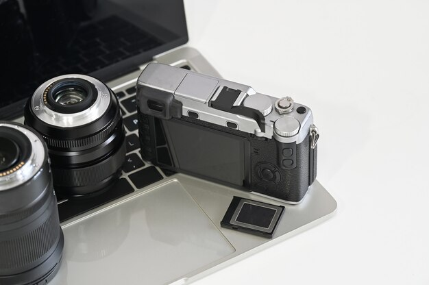 Photographer desk with camera, lens, laptop and memory