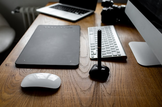 デジタルタブレットとスタイラスペンを使用して、ラップトップコンピューターで画像を描画およびレタッチする写真家。自宅のワークスペース