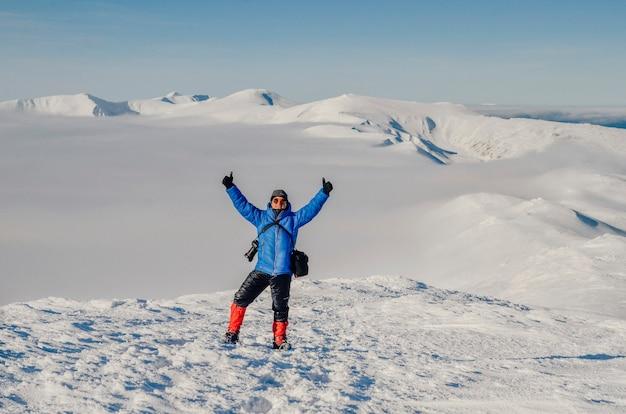 山の頂上での冬のトレッキング中の写真家。