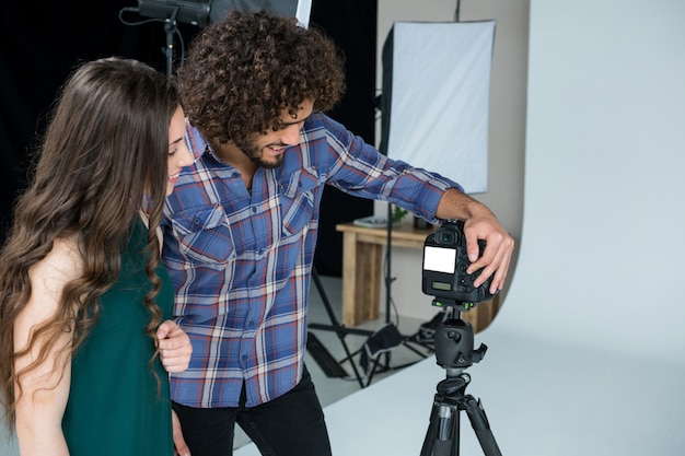 Photographer and female model reviewing captured photos in digital camera