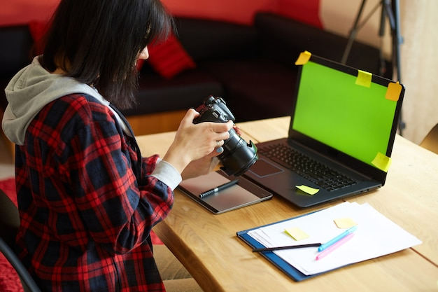 Photographer female working in a creative office holding camera, at desk and retouch photo on laptop, retoucher workplace in photo studio, successful freelance artist business, photography concept