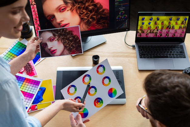 Photographer and graphic designer working in office with laptop, monitor, graphic drawing tablet and color palette.