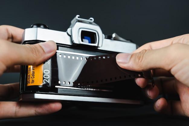 35mmフィルムを一眼レフフィルムカメラに手でロードする写真家。