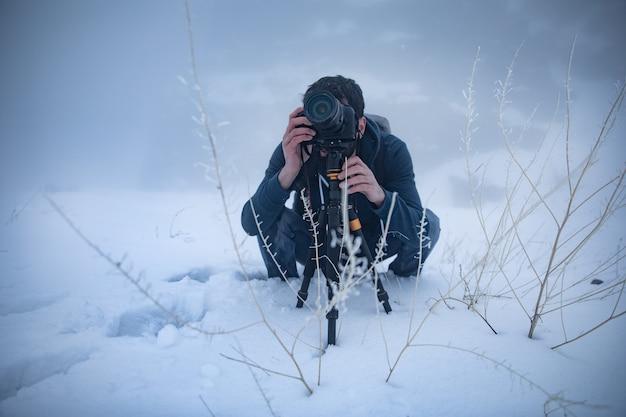 Фотограф руки держит камеру со снегом в зимний сезон