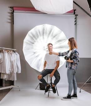 写真のポーズを取る方法で男を助けるカメラマン