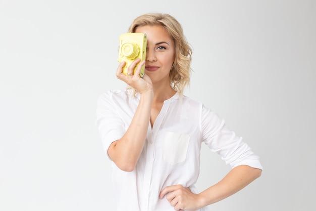 写真家、趣味、レジャーのコンセプト-コピースペースと白い壁にレトロなカメラを持つ若いブロンドの女性。