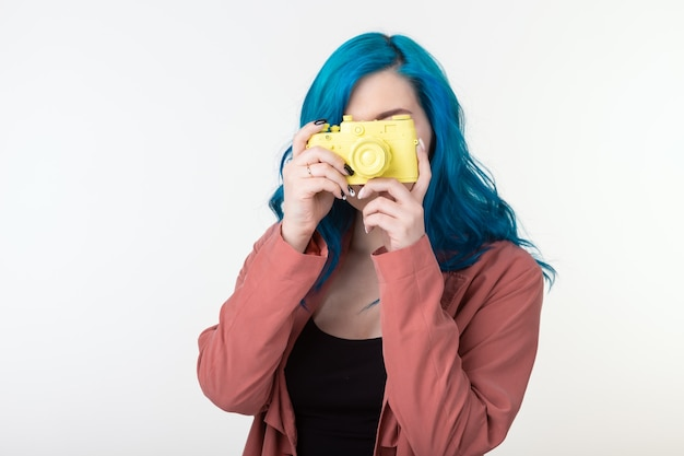 写真家、趣味、レジャーのコンセプト-コピースペースと白い壁にレトロなカメラを保持している青い髪の若い女性