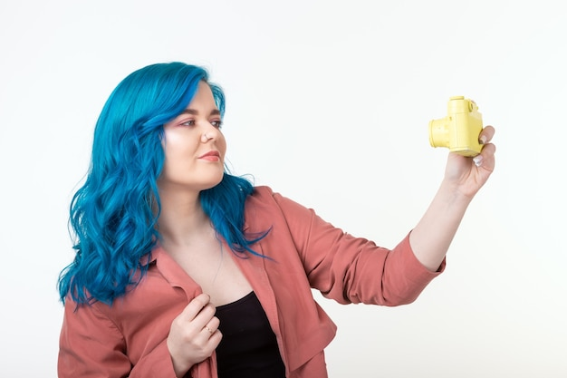 写真家、趣味、レジャーの概念-コピースペースと白い壁にレトロなカメラを保持している青い髪の若い女性