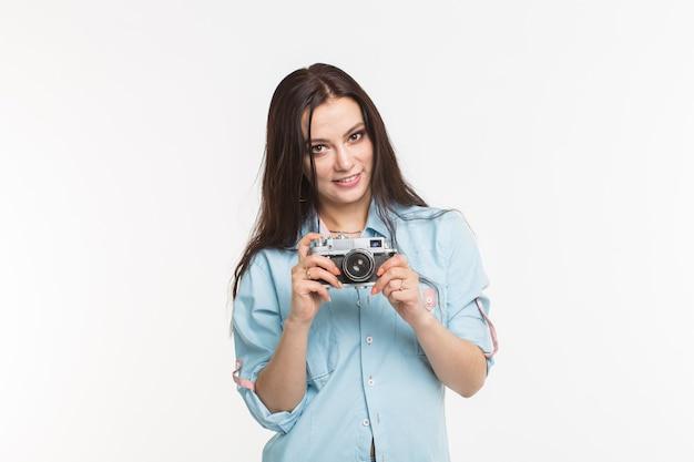 写真家、趣味と人々の概念-白い壁にレトロなカメラを持つ若いブルネットの女性。