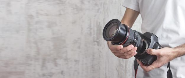 Фотограф держит камеру и объектив концепция фотографирования