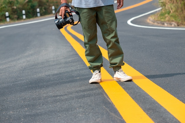 The photographer holding the camera in his hand and walking on the road