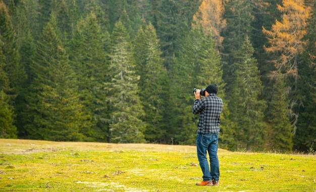 Фотограф держит камеру dslr, чтобы сделать снимок в больцано, италия.
