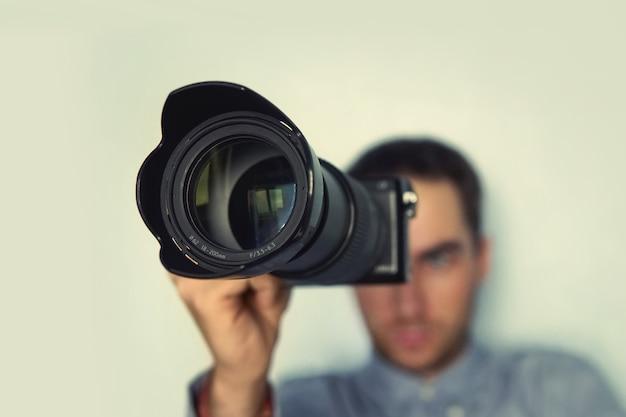 Фотограф держит беззеркальный фотоаппарат для проверки своего фото в выборочном фокусе. папарацци, фотограф наблюдает за объектом через камеру. молодой красивый фотограф с телеобъективом