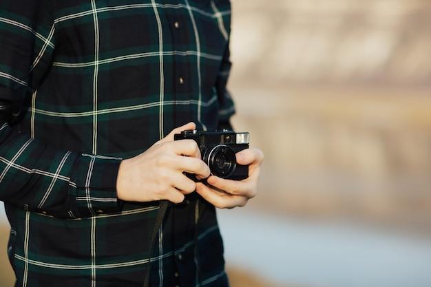 Фотограф держит в руках ретро фотоаппарат