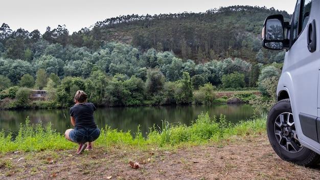 川岸の植物のマクロ写真を撮る風景の中の写真家