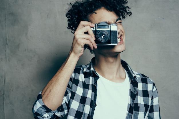 趣味のスタジオの部屋で灰色の背景にカメラを手にした格子縞のシャツを着た写真家