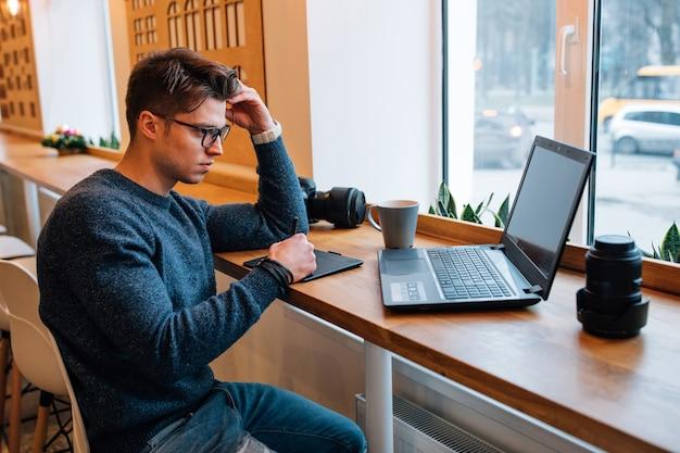 Фотограф в очках, работающих с интерактивным дисплеем пера, глядя на ноутбук