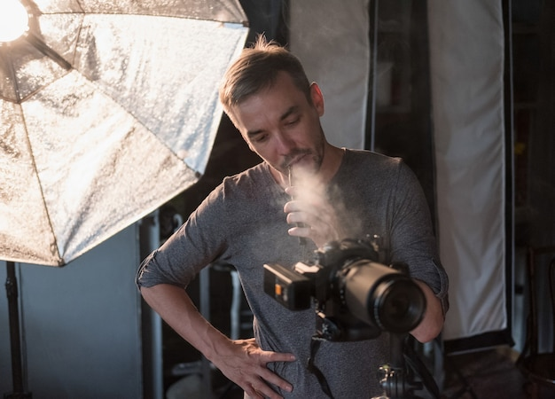 Фотограф в студии курит сигарету во время фотосессии