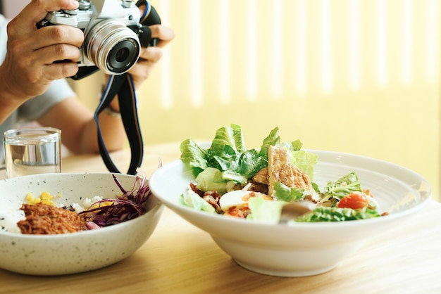 Фотограф фотографирует тарелку с салатом цезарь.