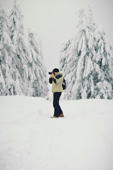 Photographer on the job among the trees on a snowy mountain