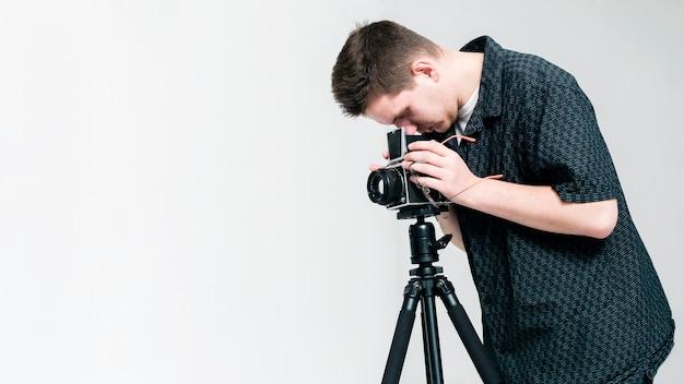 Fotografo che osserva tramite la macchina fotografica con lo spazio della copia
