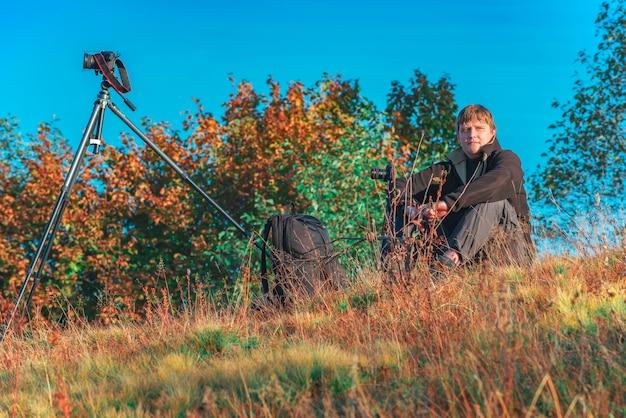 사진 작가는 가을 산 꼭대기에서 timelapses를 만듭니다.