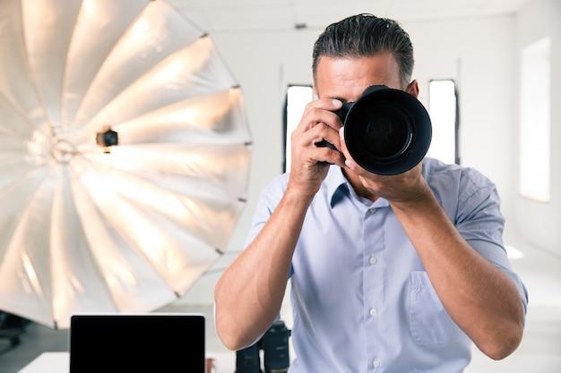 スタジオのカメラで写真を撮る写真家