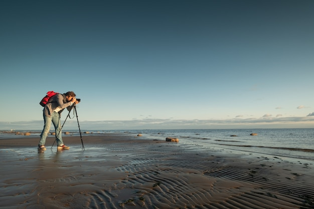 ビーチで三脚で立っている写真を作る写真家