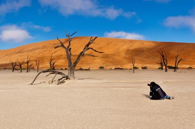Photographer making picture of landscape of dead vlei, sossusvlei, namib desert. namibia, south africa