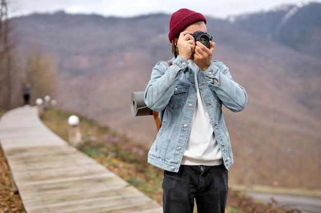 写真家の男ハイキングとトランプ。旅行と冒険のコンセプト