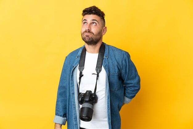 Фотограф человек изолирован на желтом фоне и смотрит вверх