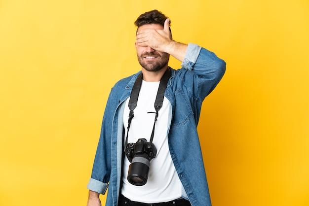 Фотограф человек изолирован на желтом фоне, закрывая глаза руками. не хочу что-то видеть