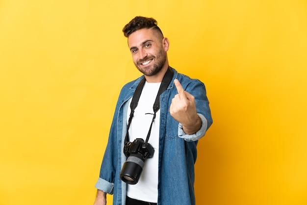 Фотограф человек изолирован на желтом фоне, делая приближающийся жест