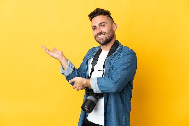 Фотограф человек изолирован на желтом фоне, протягивая руки в сторону для приглашения приехать