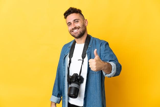 Фотограф человек изолирован на желтом фоне, показывая большой палец вверх жест