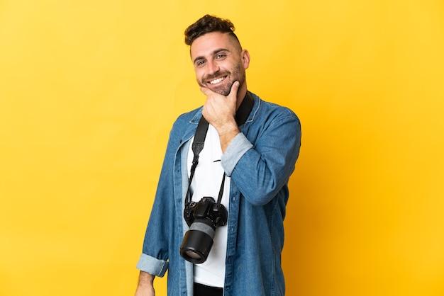 Фотограф человек изолирован на желтом фоне счастливым и улыбается