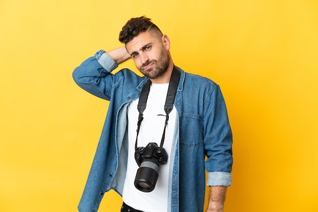 Фотограф человек изолирован на желтом фоне, сомневаясь
