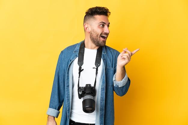 Фотограф человек изолирован на желтом фоне, намереваясь реализовать решение, подняв палец вверх