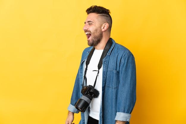Фотограф человек изолирован на желтом фоне смеется в боковом положении