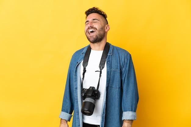 Фотограф человек, изолированные на желтом фоне смеясь