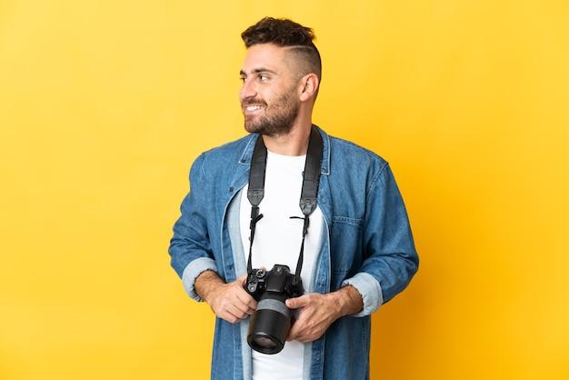 Фотограф человек изолирован на желтом фоне смотрит сторону