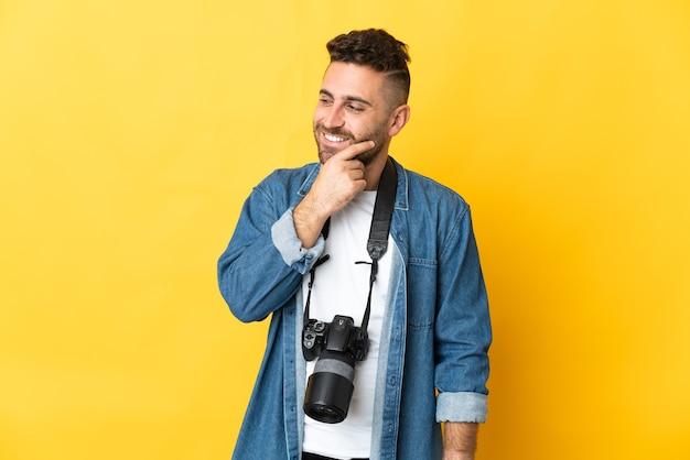 Фотограф человек изолирован на желтом фоне смотрит в сторону и улыбается