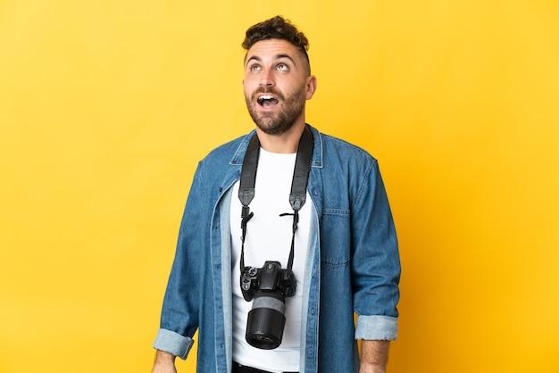 Фотограф человек изолирован на желтом фоне смотрит вверх и с удивленным выражением лица