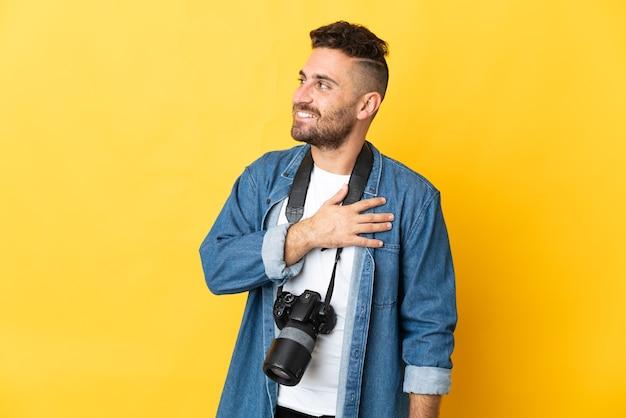 Фотограф человек изолирован на желтом фоне, глядя вверх, улыбаясь