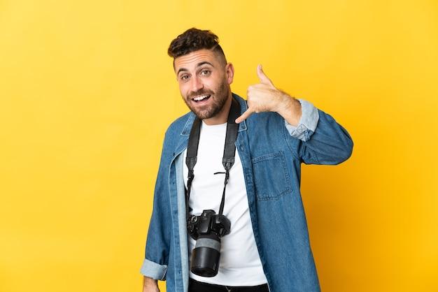Фотограф человек изолирован на желтом фоне, делая телефонный жест. перезвони мне знак