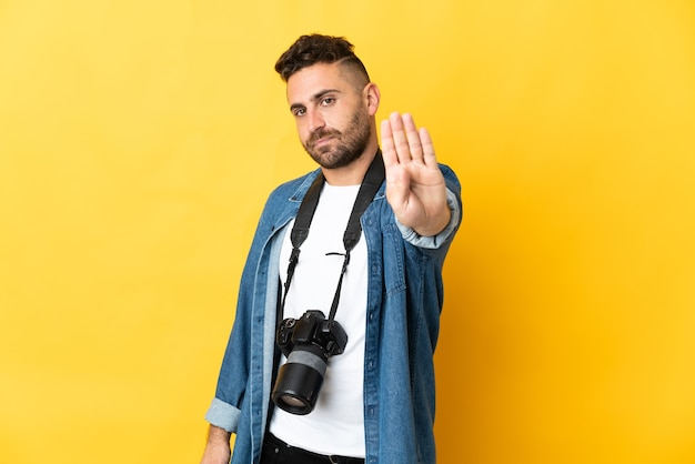 Фотограф человек изолирован на желтом фоне, делая стоп-жест