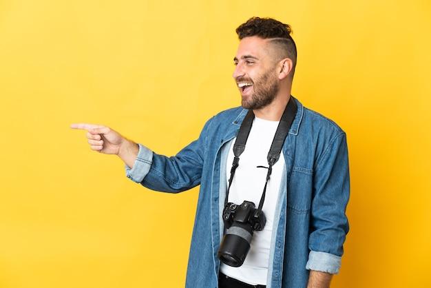 Фотограф человек изолирован на желтом фоне, указывая пальцем в сторону и представляет продукт