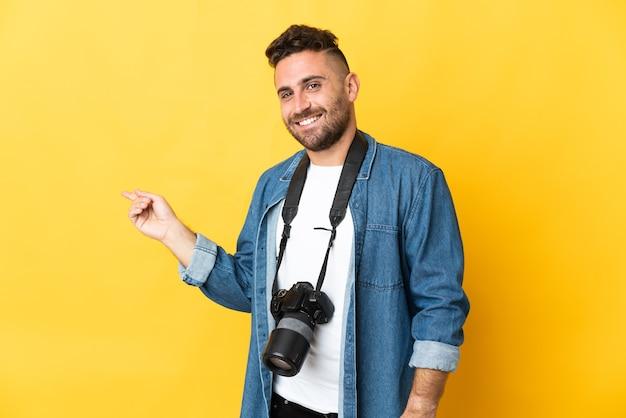 Фотограф человек изолирован на желтом фоне, указывая пальцем в сторону