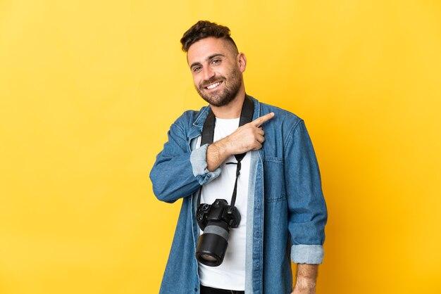 Фотограф человек изолирован на желтом фоне, указывая в сторону, чтобы представить продукт