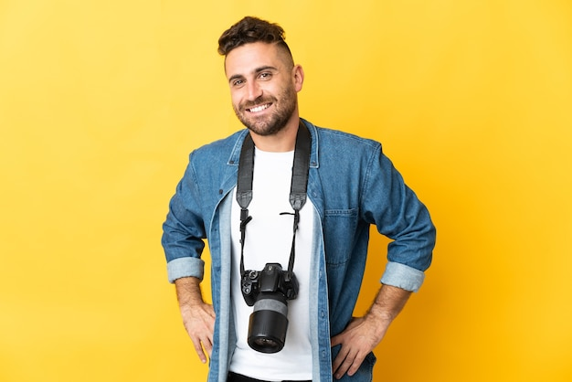 Фотограф человек изолирован на желтом фоне позирует с руками на бедрах и улыбается
